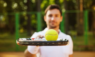 guy-holding-tennis-racket-with-ball